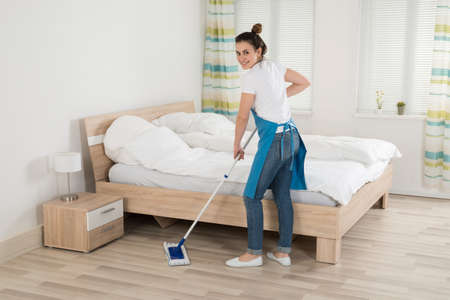 Happy Female Housekeeper Mopping Hardwood Floor In Room