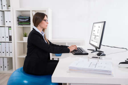 gantt: Young Businesswoman Sitting On Pilates Ball Using Computer In Office