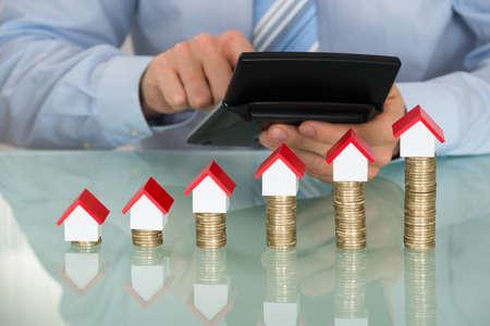 Geschäftsmann Unter Verwendung des Rechners Vor Gestapelte Münzen und Haus-Modelle