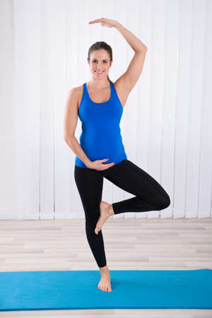 pregnancy yoga: Portrait Of Happy Pregnant Woman Doing Yoga On Exercise Mat Stock Photo