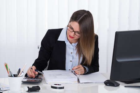 account executive: Young Businesswoman Calculating Tax At Office Desk