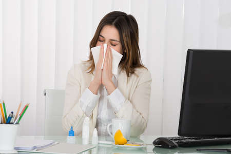 Young Businessman Blowing Her Nose In Office
