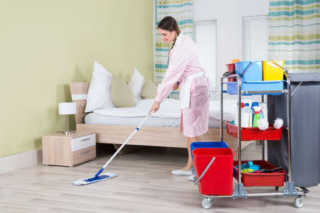 mopping: Young Female Housekeeper Mopping Floor In Room