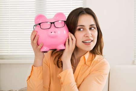 piggybank: Photo Of Smiling Young Woman Holding Piggybank Stock Photo