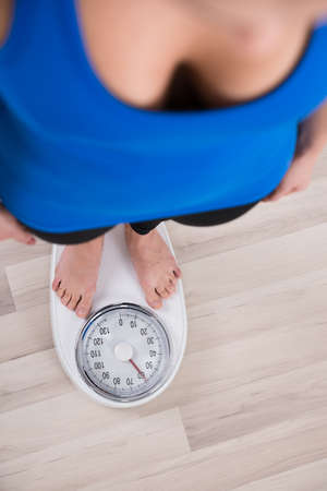 high scale: High Angle View Of Woman Measuring Body Weight On Weighing Scale