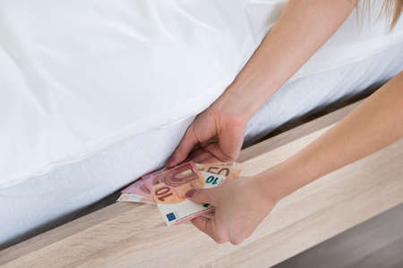 Close-up Of A Female Hand Hiding Banknotes Under Bed Stock Photo