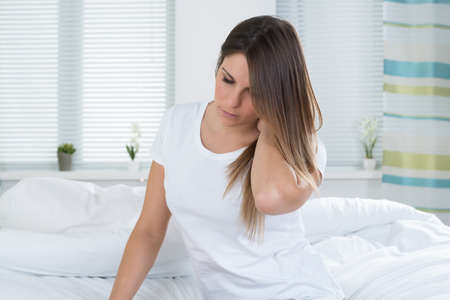 suffer: Young Woman Suffering From Neck Pain Sitting On Bed Stock Photo