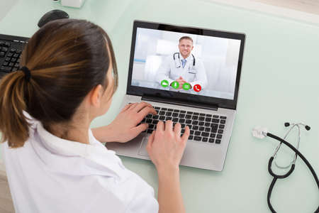 Young Female Doctor Video Chatting On Laptop In Clinic