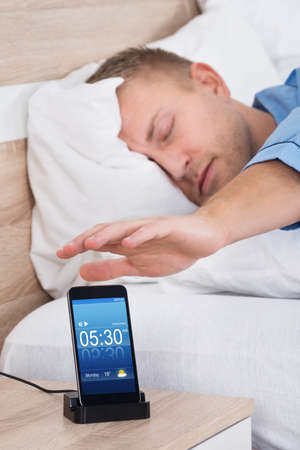 snoozing: Man Lying On Bed Snoozing Alarm On Mobile Phone Screen