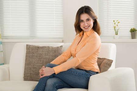 mujer sentada: Feliz joven sentado en el sofá de su sala