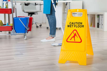 Close-up Of Female Janitor Mopping Wooden Floor With Caution Sign