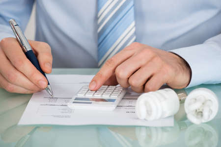 utilities: Close-up Of Businessman Using Calculator With Fluorescent Light Bulb At Desk