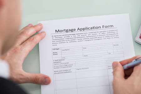 mortgage application: Close-up Of Person Hand Over Mortgage Application Form