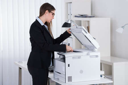 office printer: Young Businesswoman Using Printer Machine In Office