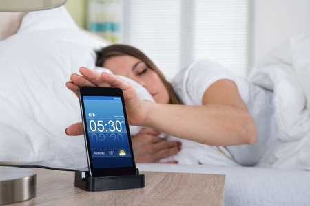snooze: Woman Lying On Bed Snoozing Alarm On Mobile Phone Screen