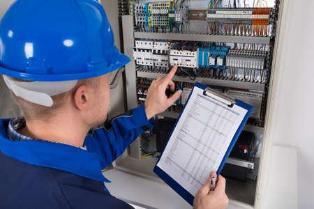 Junge Männliche Techniker Halten Zwischenablage Während Untersuchen Fusebox Standard-Bild