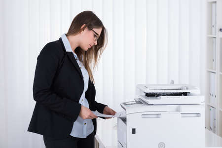photocopier: Young Businesswoman Using Copy Machine At The Office
