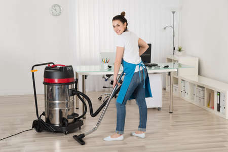 Female Janitor Cleaning Floor With Vacuum Cleaner In Office Reklamní fotografie