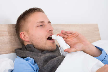 inhaler: Close-up Of Young Man Using Asthma Inhaler On His Bed