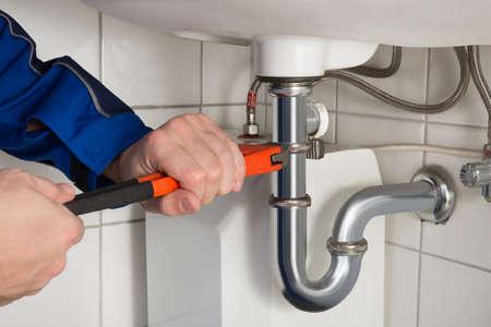 Primer Del Hombre fontanero Reparación del fregadero en cuarto de baño