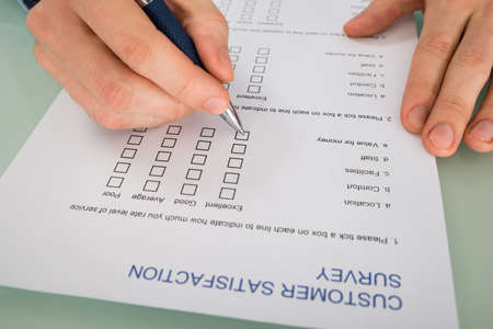 hand paper: Close-up Of Person Hand Filling Customer Satisfaction Form Stock Photo
