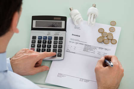 bills: Businessman Checking Invoice With Fluorescent Bulb And Calculator At Desk