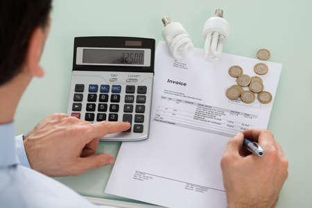 El hombre de negocios Factura Comprobación Con Bombilla fluorescente y la calculadora en el escritorio Foto de archivo