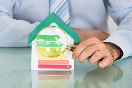 Geschäftsmann mit Vergrößerungsglas angezeigt Energy Efficiency Rate auf Haus-Modell