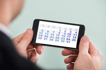 Primer plano de un hombre de negocios con el teléfono celular mirando el calendario