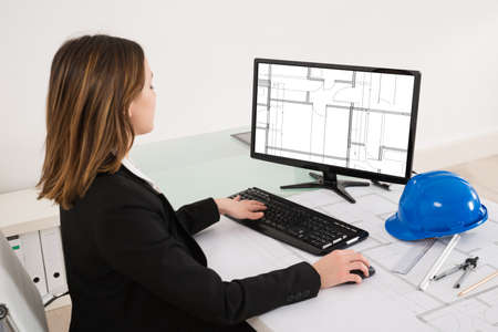 female architect: Young Female Architect Looking At Blueprint On Computer In Office