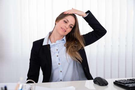 stretch: Portrait Of Happy Businesswoman Sitting At Desk