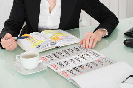 meses del año: Lista empresaria lectura de la obra en diario con el calendario en su escritorio