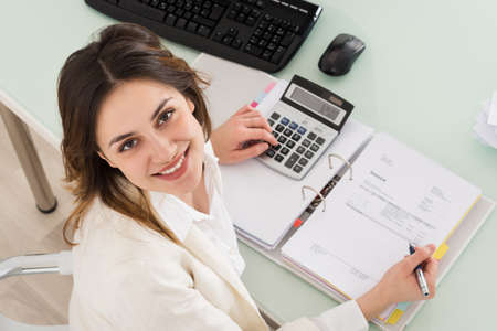 budget: Photo Of Young Businesswoman Calculating Invoice In Office