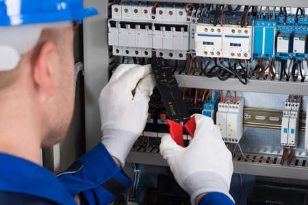 manual test equipment: Close-up Photo Of Male Electrician Repairing Fusebox