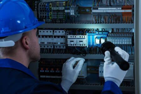 Male Technician Looking At Fusebox With Flashlight