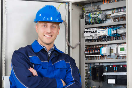 Portrait Of A Happy Young Male Electrician Standing In Front Of Fusebox