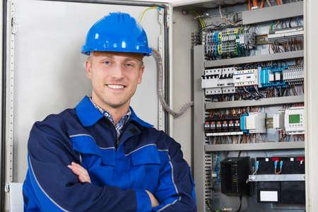Retrato de un joven feliz Hombre del electricista coloca delante de Fusebox Foto de archivo