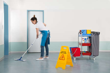 mopping: Female Janitor Mopping Corridor With Caution Sign