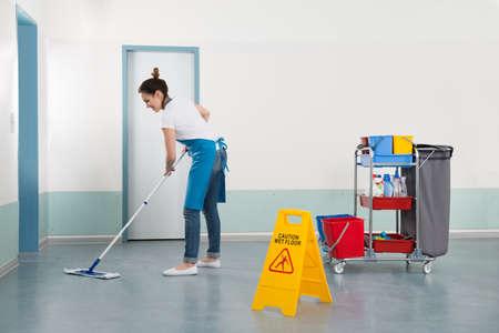 Weibliche Janitor Mopping Flur Mit Vorsicht Zeichen Standard-Bild - 52808769