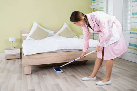 housekeeper: Young Female Housekeeper Cleaning Floor With Mop In Room