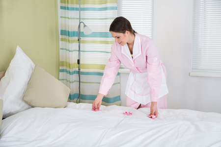 housekeeper: Happy Female Housekeeper Decorating Bed With Flowers