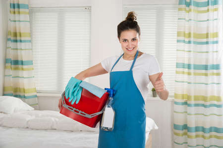 Portrait Of Happy Female Housekeeper With Cleaning Equipment