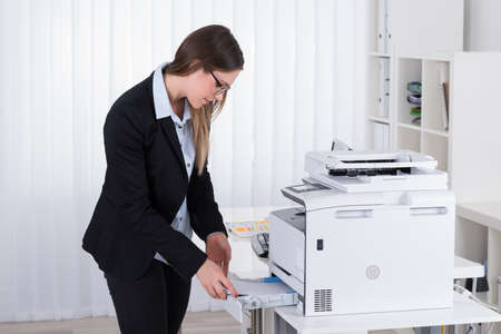 copy machine: Young Businesswoman Putting Papers In Copy Machine At Workplace Stock Photo