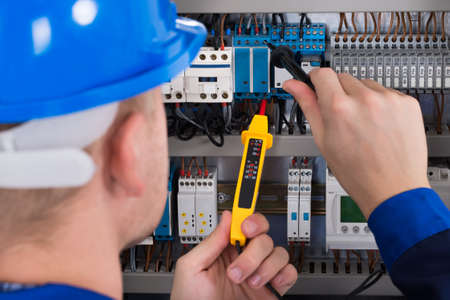 voltage: Male Electrician Examining Fusebox With Voltage Tester