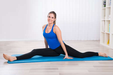 woman stretching: Happy Woman Stretching Her Leg On Exercise Mat