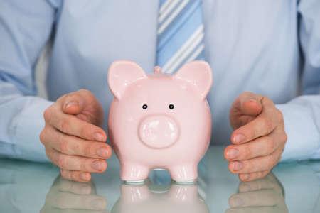 account executive: Close-up Of Businessman Hand Protecting Piggy Bank Stock Photo
