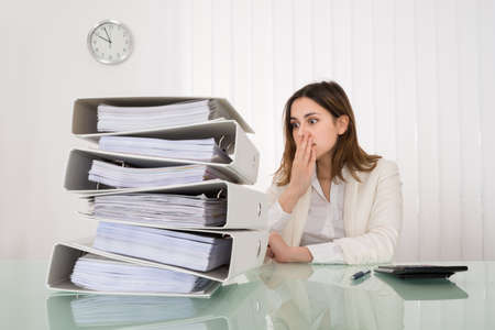 workload: Shocked Young Businesswoman Looking At Pile Of Document
