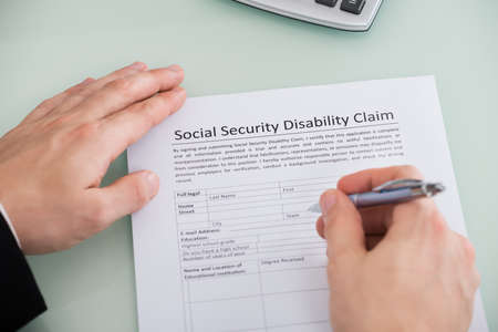 Close-up Of Person Hand Over Social Security Disability Claim Form