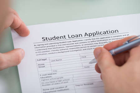 university application: Close-up Of Person Hand Over Student Loan Application Form Stock Photo