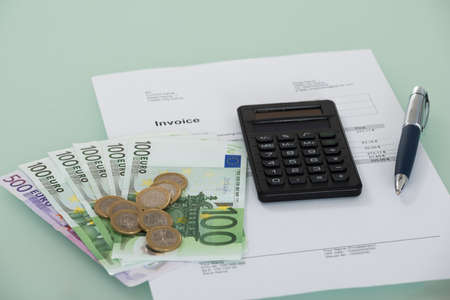 subsistence: Close-up Of Invoice And Euro Currency On Desk